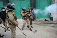 A member of India's security forces fires tear gas to disperse protesters in New Delhi (AFP Photo/Money SHARMA)