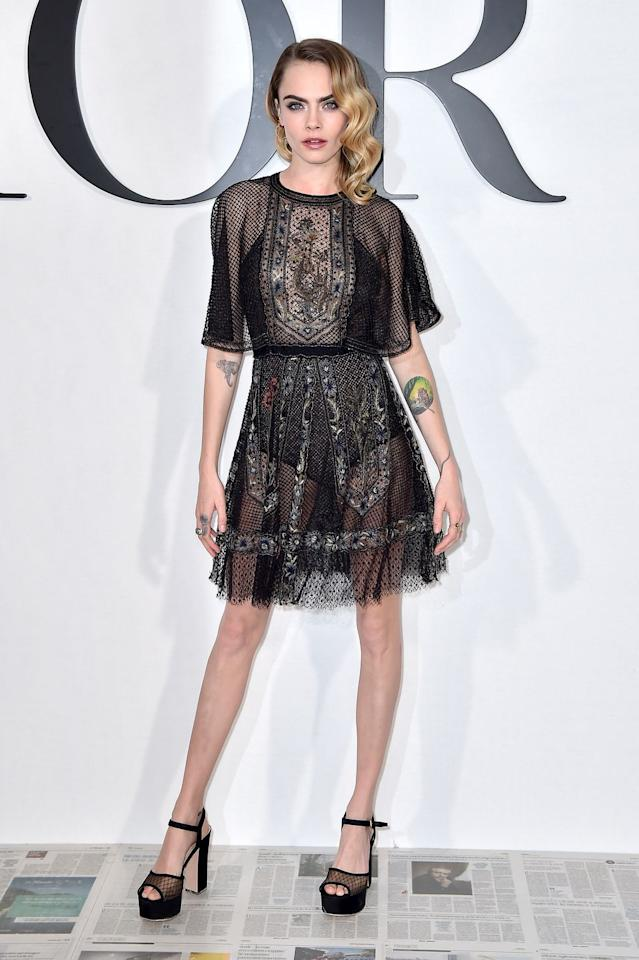<p>Cara Delevingne sat front row at Dior in a sheer dress and platform heels.</p>
