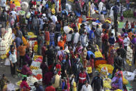 Shoppers crowd at a wholesale flower market in Bengaluru, India, Friday, Nov. 20, 2020. India's total number of coronavirus cases since the pandemic began has crossed 9 million. Nevertheless the country's new daily cases have seen a steady decline for weeks now. (AP Photo/Aijaz Rahi)