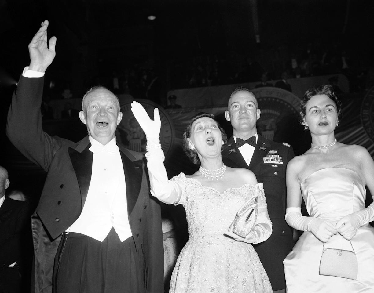 President Dwight Eisenhower and Mrs. Mamie Eisenhower wave to cheering crowd attending inaugural ball at the Statler Hotel in Washington on Jan. 21, 1957. With them is their son Maj. John Eisenhower, Mrs. Barbara Eisenhower. Ike and Mamie made the rounds of inaugural halls tonight. (AP Photo)