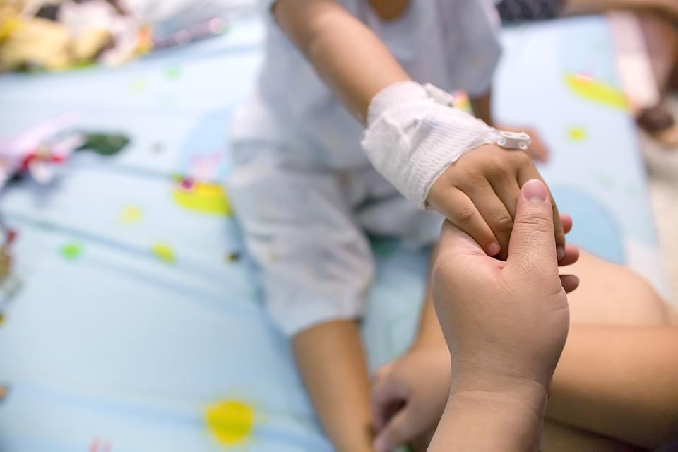 Mother holding a baby hand in hospital. Love and concern of mother