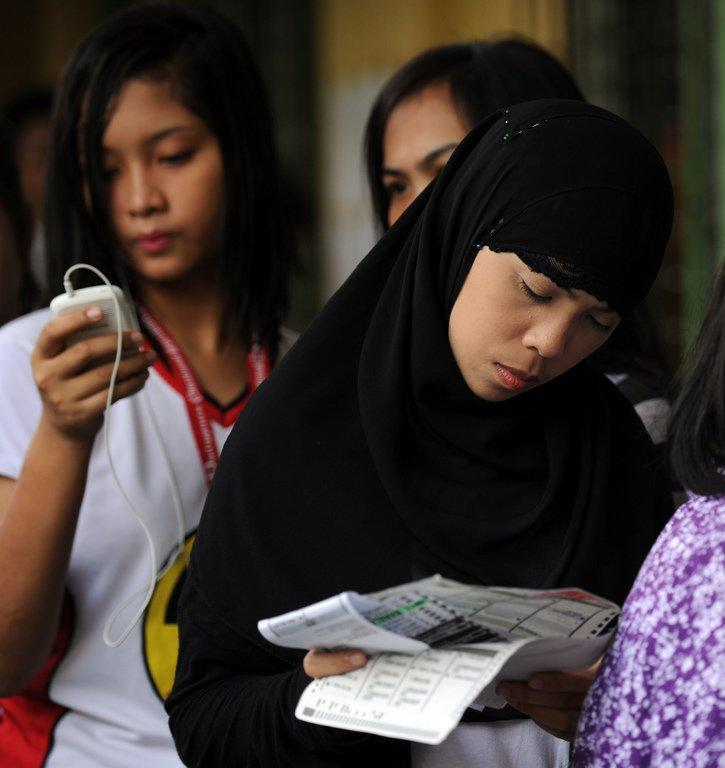 Residents queue outside a polling station during mid-term elections in Manila, on May 13, 2013. People are going to the polls to choose thousands of local leaders plus national legislators in what is seen as a referendum on the presidency of reformist Benigno Aquino