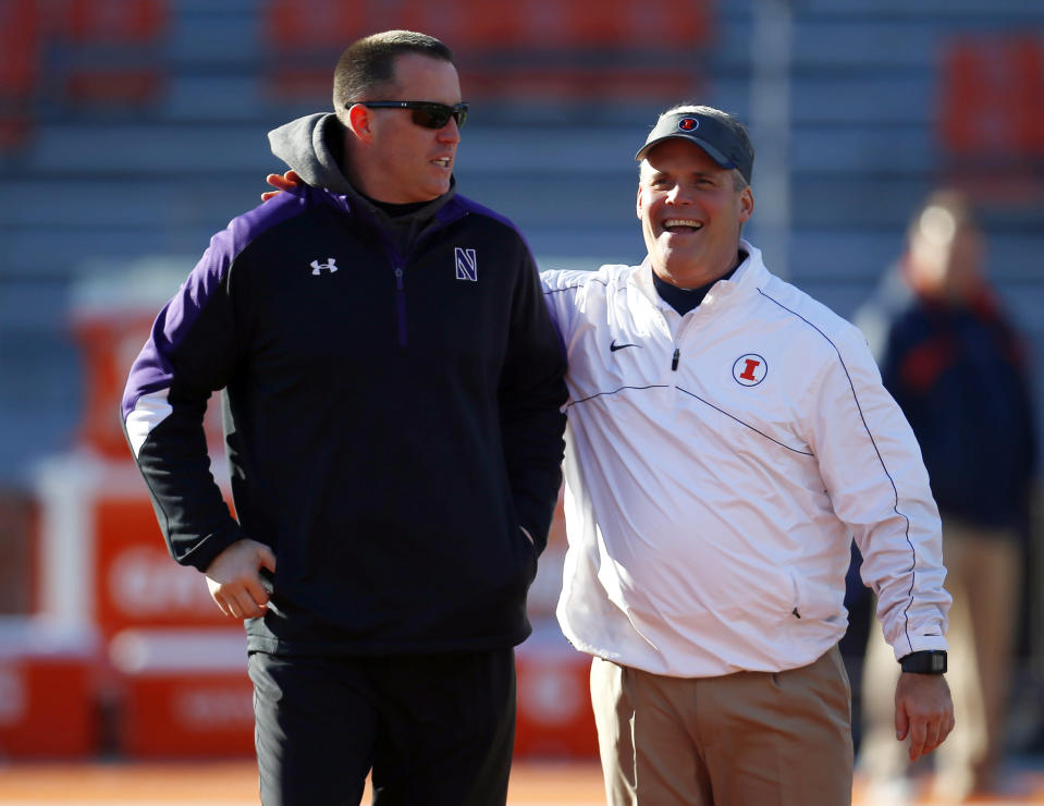 Illinois head coach Tim Beckman, right and Northwestern head coach Pat Fitzgerald, left, talk with each other before their teams NCAA college football game on Saturday, Nov. 30, 2013, in Champaign, Ill. (AP Photo/Jeff Haynes)