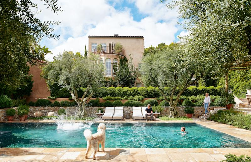 At their Los Angeles home, designers Alexandra (right) and Michael Misczynski of AD100 firm Atelier AM gather by the pool with their sons and dog.