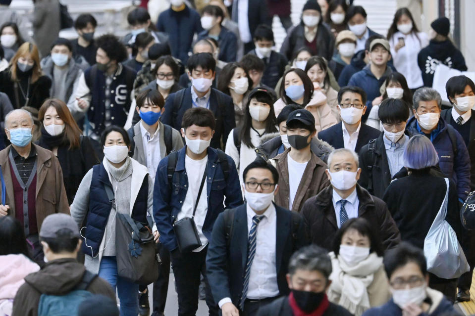 People wear face masks as they make their way through a street in Tokyo Friday, Nov. 27, 2020. Tokyo reported 570 new COVID-19 cases on Friday, a new record for Japan's capital city as the country faces a surge in infections. (Yohei Nishimura/Kyodo News via AP)