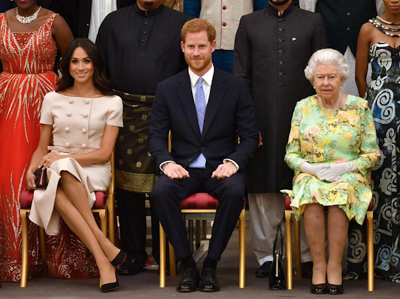 Queen Elizabeth, Prince Harry and Meghan, the Duchess of Sussex pose for a picture with some of Queen's Young Leaders at a Buckingham Palace reception on June 26.   (POOL New / Reuters)