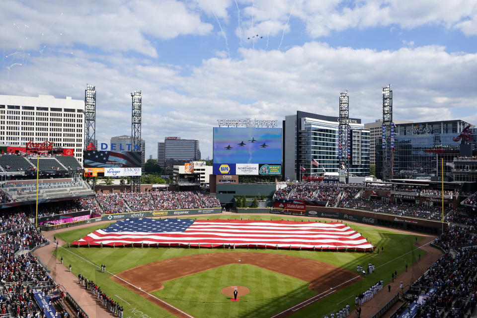 A giant United States flag is stretched across the outfield of Truist Park as military jets fly overhead in observance of Memorial Day before a baseball game between the Washington Nationals and the Atlanta Braves, Monday, May 31, 2021, in Atlanta. (AP Photo/John Bazemore)