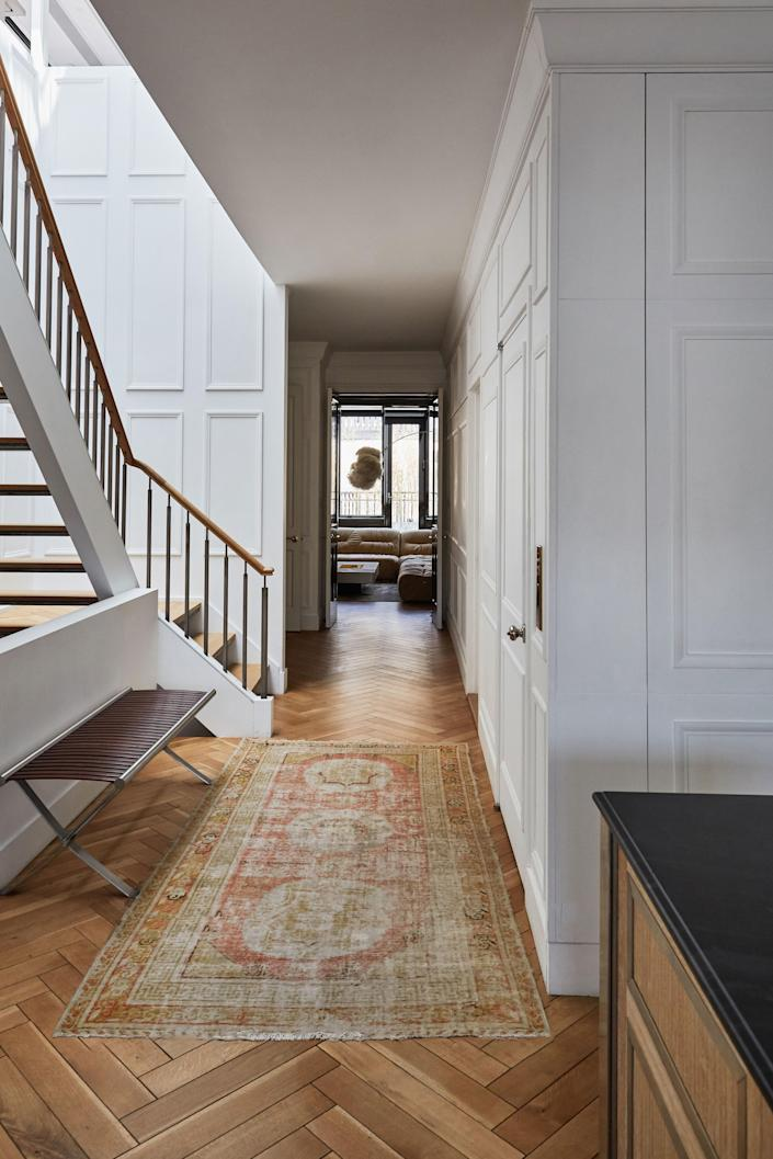 Blinken removed the existing carpeting and replaced it with herringbone floors. The rug seen here came from an auction at Bonhams. At the end of the hall is the library.