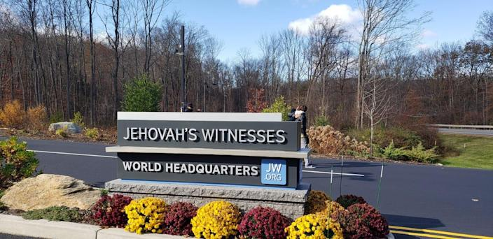 A sign marks the entrance of the Jehovah's Witness world headquarters in Tuxedo Park, New York.