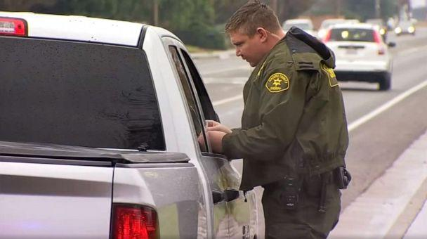 PHOTO: A deputy with the Madera County Sheriff's Department in Central California gives a motorist a holiday card containing $100 as part of a holiday outreach program, Dec. 23, 2019. (KFSN)