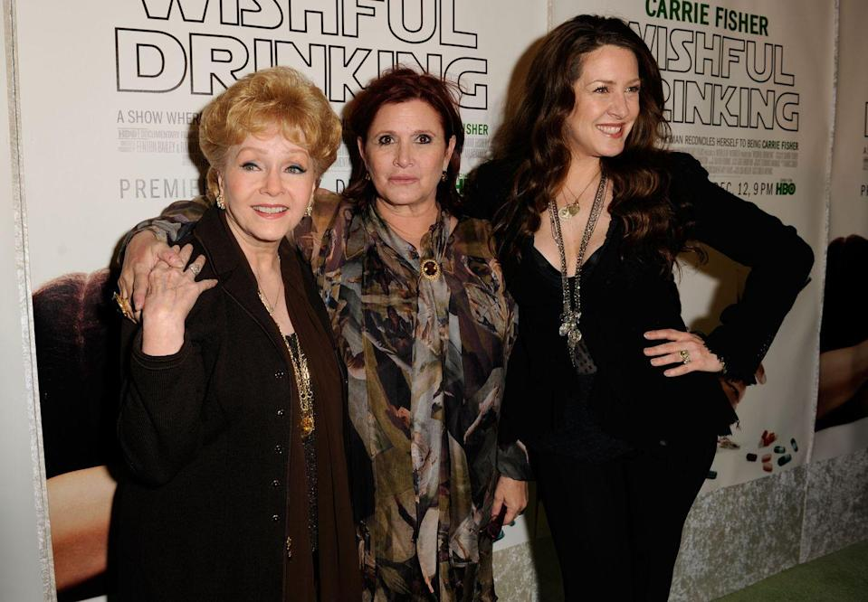 "<p>On the tails of a successful performance and best-selling book, Carrie partnered with HBO to air a <a href=""https://carriefisher.com/about/"" rel=""nofollow noopener"" target=""_blank"" data-ylk=""slk:special performance of her one-woman show"" class=""link rapid-noclick-resp"">special performance of her one-woman show</a>. Here, she's seen at the premiere with her mother, Debbie Reynolds, and half sister, Joely Fisher. </p>"