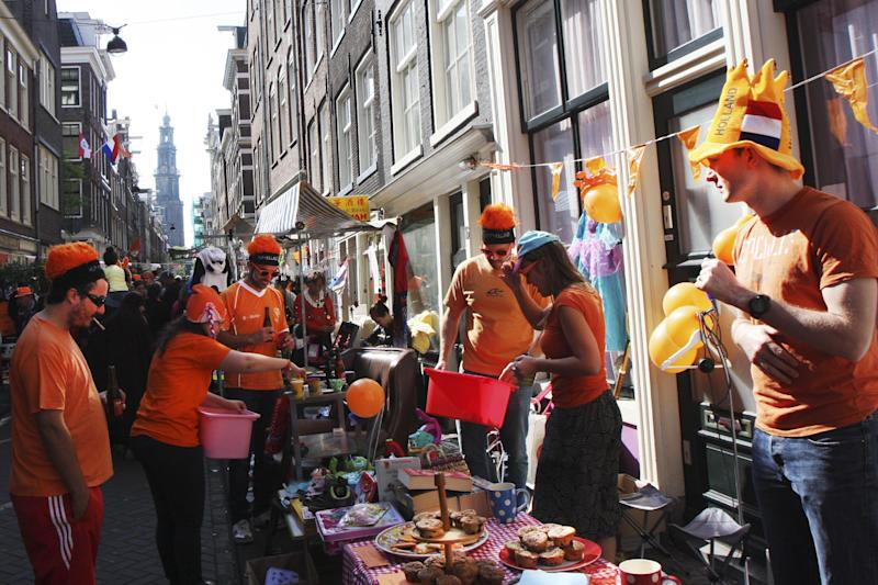 People celebrate King's Day in Amsterdam, Netherlands, Saturday, April 26, 2014. The Dutch celebrate the first ever King's Day, a national holiday held in honor of the newly installed monarch, King Willem Alexander. King's Day replaces the traditional Queen's Day. (AP Photo/Margriet Faber)