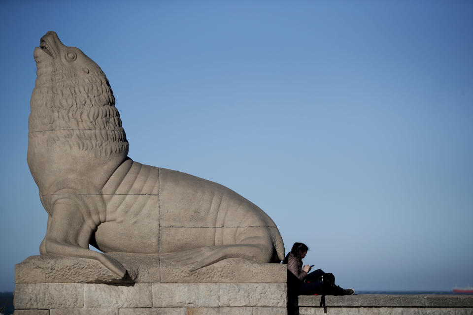 A woman sits next to a statue of a sea lion on the waterfront during the COVID-19 pandemic in Mar del Plata, Argentina, Saturday, Oct. 10, 2020. A recent decree from President Alberto Fernández extended quarantine measures in Argentina yet again and Mar del Plata was one of the places ordered to remain in social, preventive and mandatory isolation at least until Oct. 25. (AP Photo/Natacha Pisarenko)