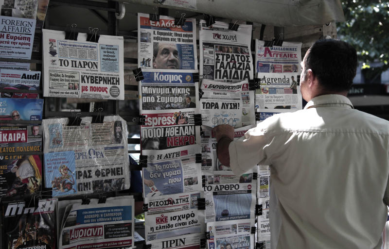 A man looks at the front pages of newspapers the day before general elections in Thessaloniki, Greece, Saturday, June 16, 2012. Greeks vote for the second time in six weeks Sunday amid fears that the country could be forced out of the euro if they reject the strict austerity measures taken in return for billions of euros in rescue loans from other European countries and the International Monetary Fund. (AP Photo/Dimitri Messinis)