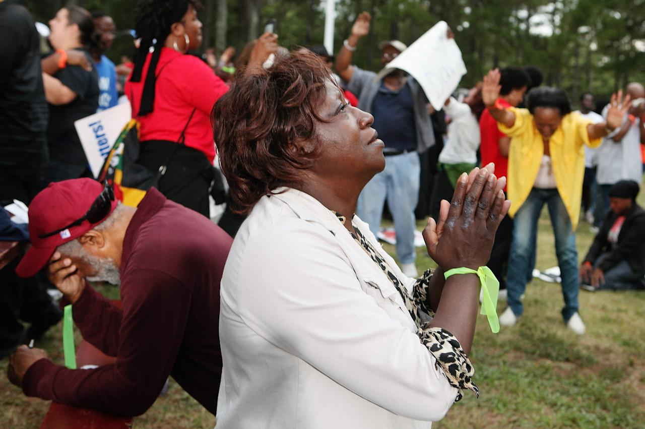 JACKSON, GA - SEPTEMBER 21:   Lillie Sutton (C) prays after hearing that there is a delay, not a stay, in the execution of Troy Davis as protestors gather at Jackson State Prison for the planned execution of inmate Troy Davis on September 21, 2011 in Jackson, Georgia.  The Georgia Board of Pardons and Paroles denied clemency for death row inmate Troy Davis on Tuesday morning.  Davis is scheduled for execution at 7pm on Wednesday, September 21, 2011 for the 1989 slaying of off-duty Savannah, Ga., police officer Mark MacPhail. Controversy over Davis' guilt has drawn national attention to the case.  (Photo by Jessica McGowan/Getty Images)