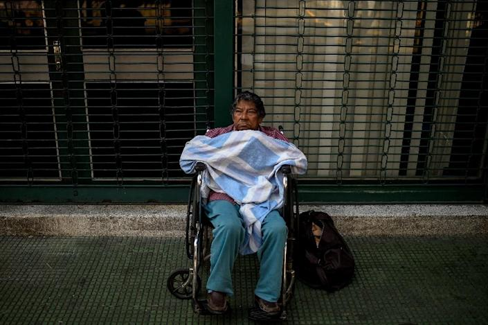 A patient on dialysis treatment waits outside a closed clinic during a power outage in Caracas on March 26, 2019 (AFP Photo/Federico PARRA)