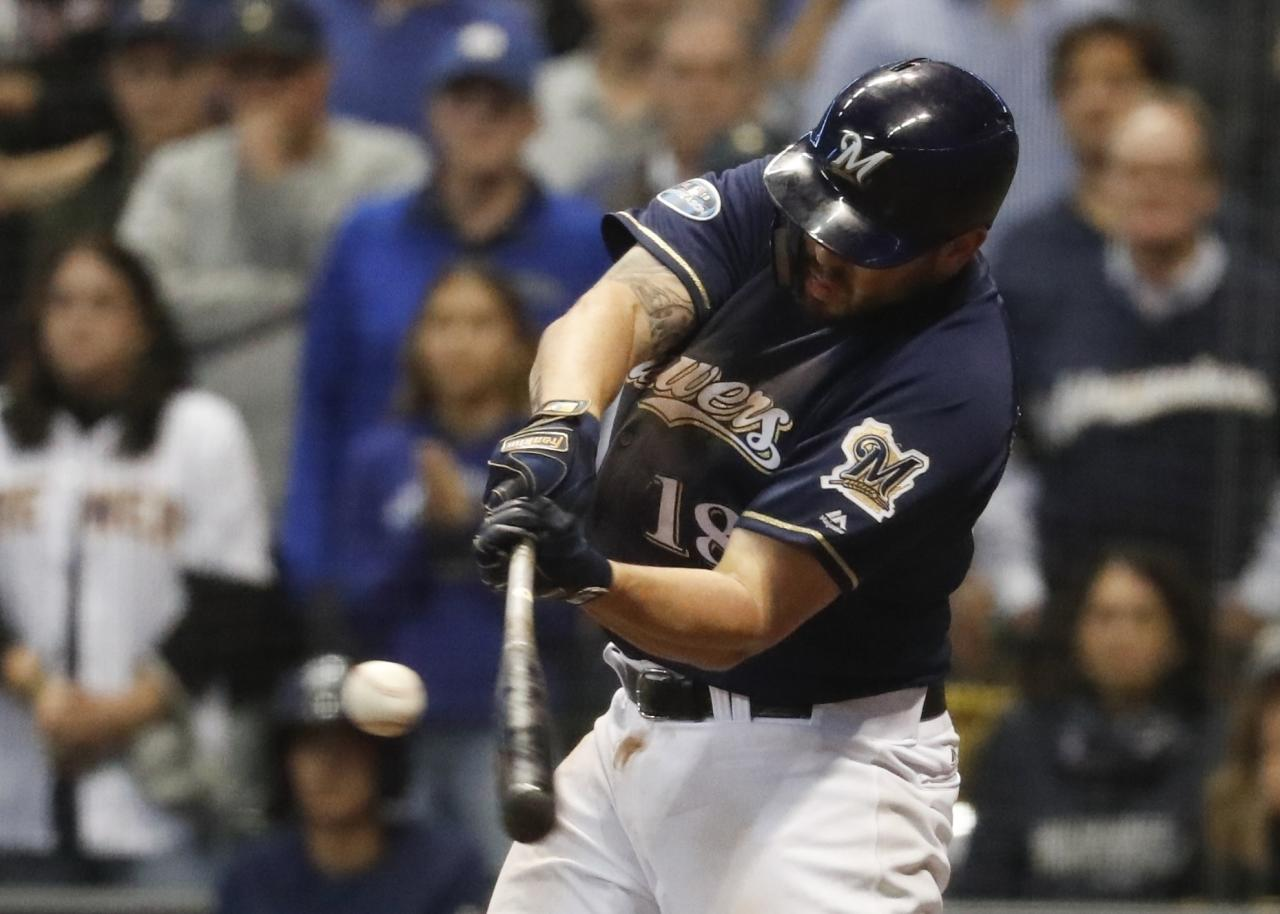 FILE - In this Oct. 5, 2018, file photo, Milwaukee Brewers' Mike Moustakas hits an RBI single during the eighth inning of Game 2 of the National League Divisional Series baseball game against the Colorado Rockies in Milwaukee. A person familiar with the negotiations says Moustakas and the Brewers are nearing a deal that would keep the third baseman in Milwaukee for a guarantee of about $10 million. The person spoke to The Associated Press on condition of anonymity Sunday, Feb. 17, 2019, because the agreement will be subject to a successful physical. (AP Photo/Jeff Roberson, File)
