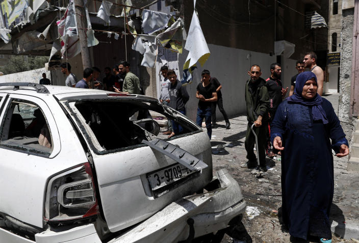 Image: Residents gather around a car that was hit in an Israeli airstrike that killed three people in the car, on the main road in Gaza City (Adel Hana / AP)