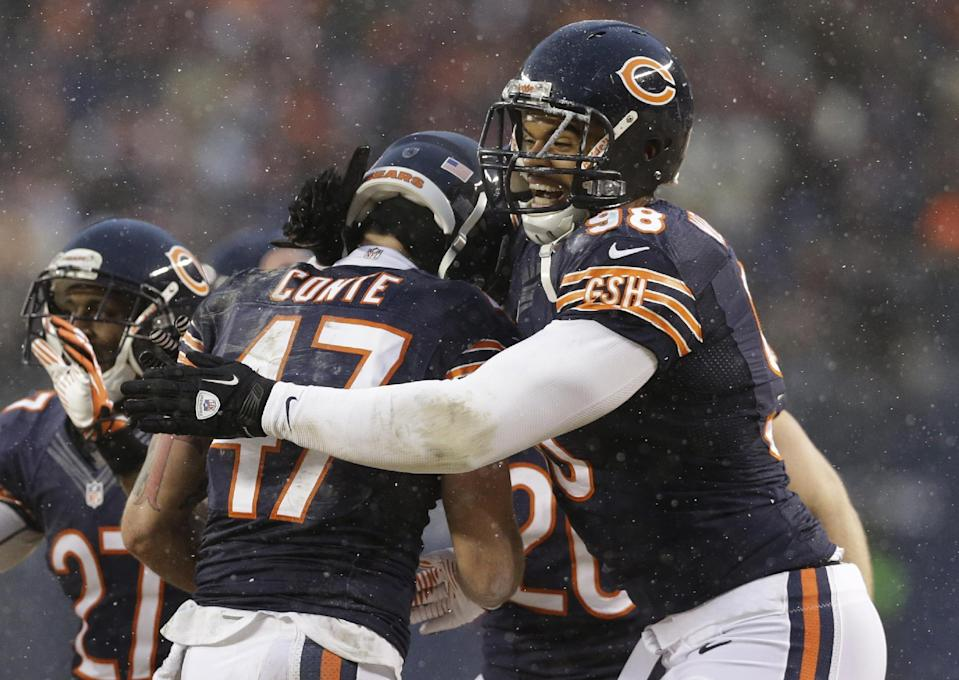 Chicago Bears safety Chris Conte (47) celebrates with defensive tackle Corey Wootton (98) after intercepting a pass during the first half of an NFL football game against the Green Bay Packers, Sunday, Dec. 29, 2013, in Chicago. (AP Photo/Nam Y. Huh)