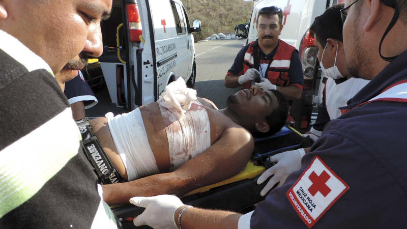 Emergency workers treat an injured man after a shootout with vigilantes fighting the Knights Templar cartel left five dead, at least two injured and several detained on the outskirts of the seaport of Lazaro Cardenas, western Mexico, Sunday April 27, 2014. Prosecutors in western Michoacan state confirmed Monday that the five dead belonged to a pseudo-vigilante group that had been financed by the gang to stem the advance of the self-defense movement. (AP Photo/Agencia Esquema)
