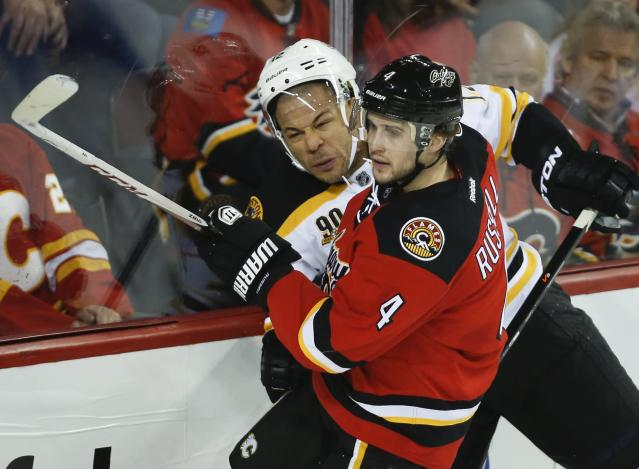 Boston Bruins' Jarome Iginla, left, tries to get past Calgary Flames' Kris Russell during the second period of an NHL hockey game in Calgary, Alberta, Tuesday, Dec. 10, 2013. (AP Photo/The Canadian Press, Jeff McIntosh)