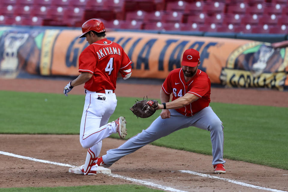 Cincinnati Reds' Shogo Akiyama (4) is out at first base as Matt Davidson (64) fields the ball during an intrasquad baseball game in Cincinnati, Tuesday, July 14, 2020. (AP Photo/Aaron Doster)