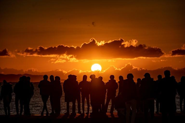 People gather at Southern Beach of Chigasaki to watch the sunrise on New Year's Day in Kanagawa Prefecture, southwest of Tokyo on January 1, 2021