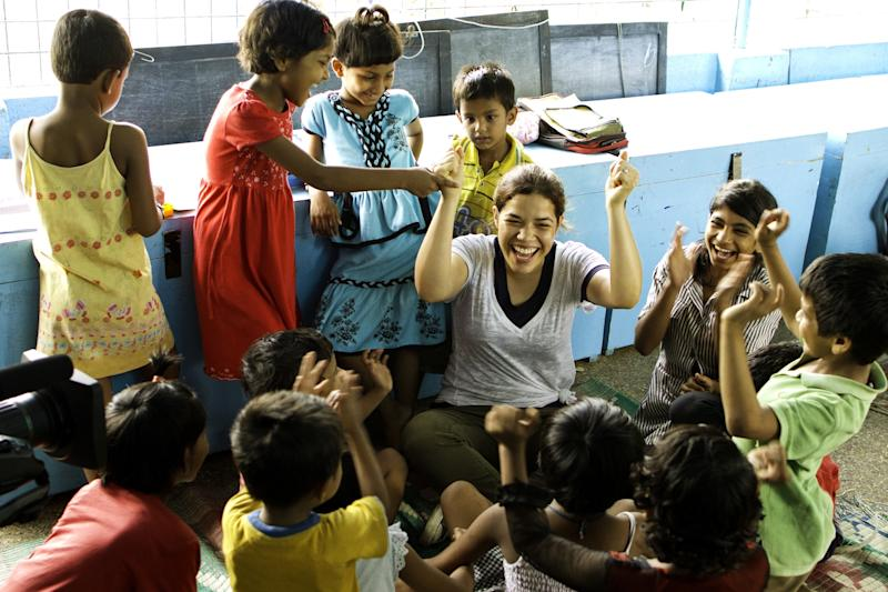 """This undated image provided by PBS shows actress America Ferrara interacting with kids in Kolkata, India. Ferrara, Meg Ryan and Olivia Wilde are among the actresses who brought their star power to the PBS documentary """"Half the Sky,"""" which details efforts to help exploited women worldwide. It airs Monday and Tuesday, Oct. 1-2. (AP Photo/PBS, David Smoler)"""