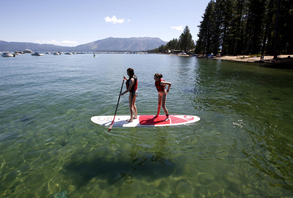 FILE - In this Aug. 20, 2019, file photo, Freya Mayo, left, and her sister Evie, of London, try out a paddle board on Lake Tahoe near South Lake Tahoe, Calif. With wildfire no longer threatening Lake Tahoe, residents, tourists and scientists drawn to its clean alpine air, clear blue waters and fragrant pine trees now wonder about the long-term effects that will remain after wildfire season ends. (AP Photo/Rich Pedroncelli, File)