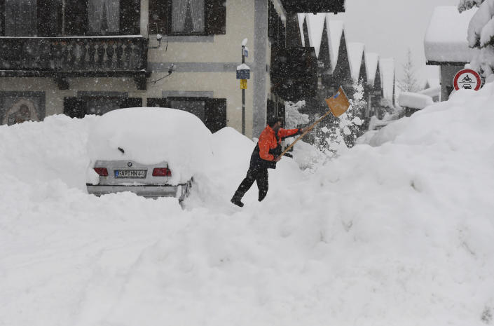 A man shovels his car free of snow after days of snowfall in Garmisch-Partenkirchen, southern Germany, Monday, Jan. 18, 2021. (Angelika Warmuth/dpa via AP)
