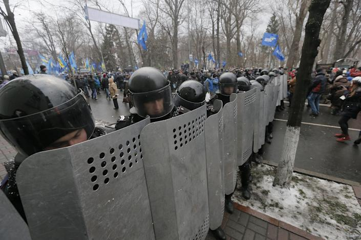 Riot police protect government buildings from the Pro-European Union activists, pro-Presidential supporters behind them, in Kiev, Ukraine, Sunday, Dec. 8, 2013. The third week of protests continue Sunday with an estimated 200,000 Ukrainians occupying central Kiev to denounce President Viktor Yanukovych's decision to turn away from Europe and align this ex-Soviet republic with Russia. (AP Photo/Efrem Lukatsky)