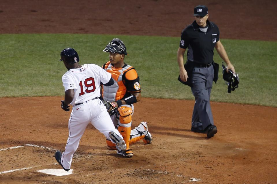 Boston Red Sox's Jackie Bradley Jr. (19) scores in front of Baltimore Orioles' Pedro Severino on a double by Jose Peraza during the third inning of an opening day baseball game at Fenway Park, Friday, July 24, 2020, in Boston. (AP Photo/Michael Dwyer)