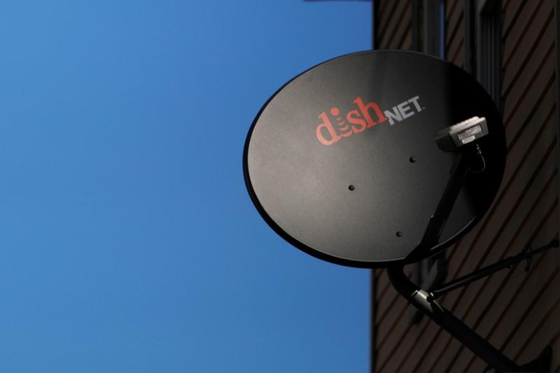 A Dish Network receiver hangs on a house in Somerville
