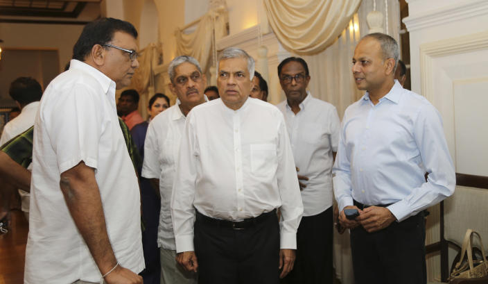 Sri Lanka's sacked prime minister Ranil Wickremesinghe, center, speaks with party members at his official residence in Colombo, Sri Lanka, Friday, Oct. 26, 2018. Sri Lankan President Maithripala Sirisena has sacked the country's prime minister and replaced him with a former strongman, state television said Friday. (AP Photo/Rukmal Gamage)