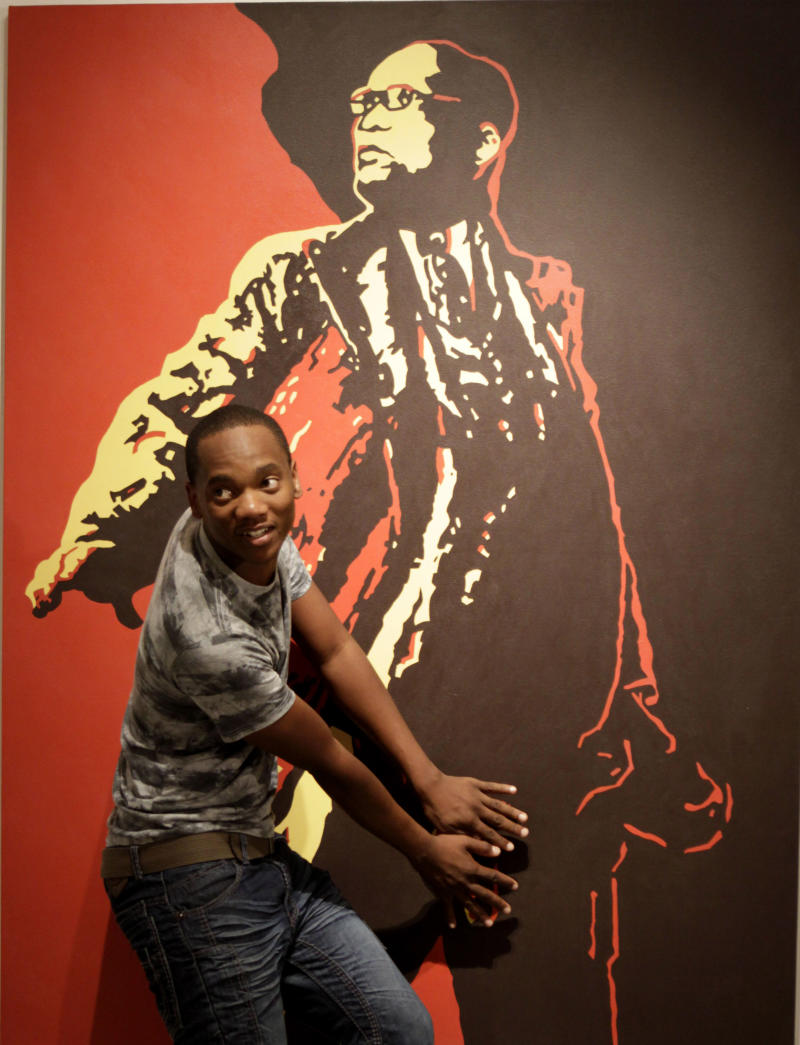 "File -  In this Friday, May 18, 2012 file photo a visitor to the Goodman Gallery in Johannesburg holds his hands over what could be a codpiece accentuating the genitals on a painting entitled ""The Spear"" depicting President Jacob Zuma, by South African artist Brett Murray. South Africa's Film and Publication Board on Wednesday Oct. 10 2012, declassified the  painting, which outraged supporters of  Zuma when it was displayed,  is no longer deemed offense to public taste. (AP Photo / Denis Farrell, file)"