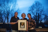 """Jeff and Lola Carter stand with their daughter, Amanda, and a framed photo of Kayla, their daughter who struggled with drug addiction, Tuesday, March 16, 2021, at their home in Milton, W.Va. Kayla was hospitalized in June with endocarditis, a heart infection common among injection drug users. It seemed like she was suddenly determined to live. In October, her mother couldn't reach her one Friday. She went to her apartment, and found her dead on her bathroom floor. They are still waiting for the medical examiner's report, but her father would rather never see it. It brings him comfort to think she died from a complication from her surgeries, and not that she relapsed and overdosed. Either way, the drugs killed her, he said. """"The only thing about any of it gives me any relief at all,"""" he says, """"is knowing we're not the only ones."""" (AP Photo/David Goldman)"""