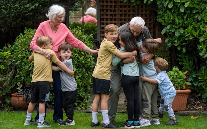 Great-grandfather and great-grandmother Alan and Jennifer Grover are greeted by some of their great-grandchildren with a mass cuddle on the day Covid-19 restrictions are lifted - Paul Grover for The Telegraph