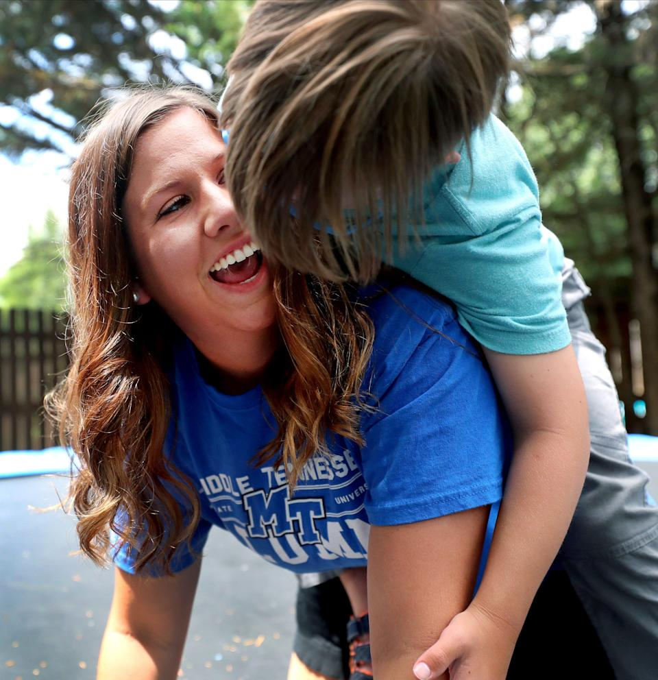 Eli Kellum, 7, climbs on the back of babysitter Missy Wood in the Kellum family's backyard in Murfreesboro on June 18, 2020, as the two play on the trampoline. Wood has been looking for work since April but has not been able to find any child-focused social work positions since graduating from MTSU in May. After the pandemic hit, job postings for her planned career seemed to disappear.