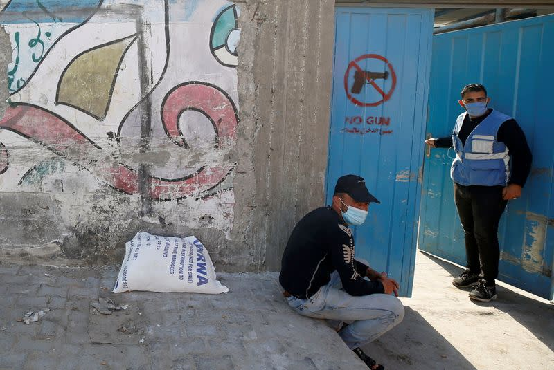 Palestinian worker stands at the entrance gate of an aid distribution center run by the United Nations Relief and Works Agency (UNRWA), at Beach refugee camp in Gaza City