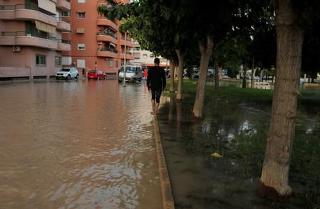 A man tries to avoid the water as he walks through a flooded street in Orihuela