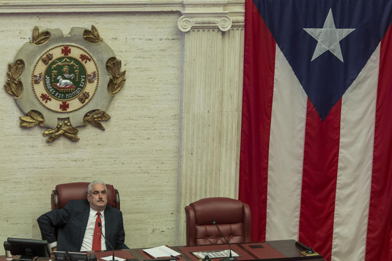 Puerto Rico Senate President Thomas Rivera Schatz sits in his chair at the Senate as discussions go on for the confirmation of Secretary of State Pedro Pierluisi as Puerto Rico's new Governor, in San Juan, Puerto Rico, Thursday, August 1, 2019. Puerto Rico's governing party was in full-blown crisis as the confirmation of Pierluisi was delayed into next week, casting doubt over exactly who will become governor when Gov. Ricardo Rossello leaves office. Pierluisi's main obstacle appeared to be Rivera Schatz, who has said he won't vote for Rosselló's nominee and wants to run for governor himself next year. (AP Photo/Dennis M. Rivera Pichardo)