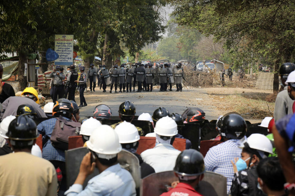 Anti-coup protesters stay behind a makeshift barricade during a demonstration as police prepare to fire tear gas in Naypyitaw, Myanmar, Monday, March 8, 2021. The escalation of violence in Myanmar as authorities crack down on protests against the Feb. 1 coup is raising pressure for more sanctions against the junta, even as countries struggle over how to best sway military leaders inured to global condemnation.(AP Photo)