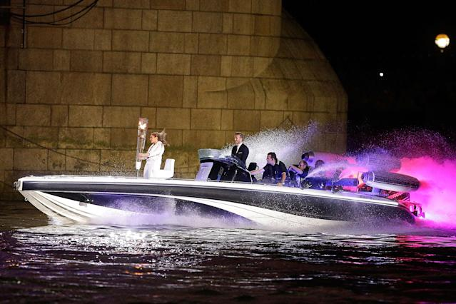 LONDON, ENGLAND - JULY 27: David Beckham passes under Tower Bridge driving a speedboat named 'Max Power' which carries the Olympic Torch with its torchbearer on July 27, 2012 in London, England. Athletes, heads of state and dignitaries from around the world have gathered in the Olympic Stadium for the opening ceremony of the 30th Olympiad. London plays host to the 2012 Olympic Games which will see 26 sports contested by 10,500 athletes over 17 days of competition. (Photo by Matthew Lloyd/Getty Images)