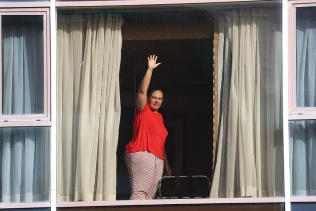 A hotel guest waves to members of the media from the window of Radisson Blu Edwardian Hotel