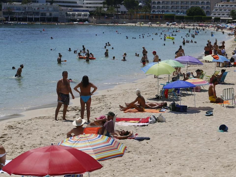 People enjoy Magaluf beach in Mallorca. Britons are surprised at the abrupt announcement to impose a two-week quarantine on people travelling to the UK from Spain: Reuters