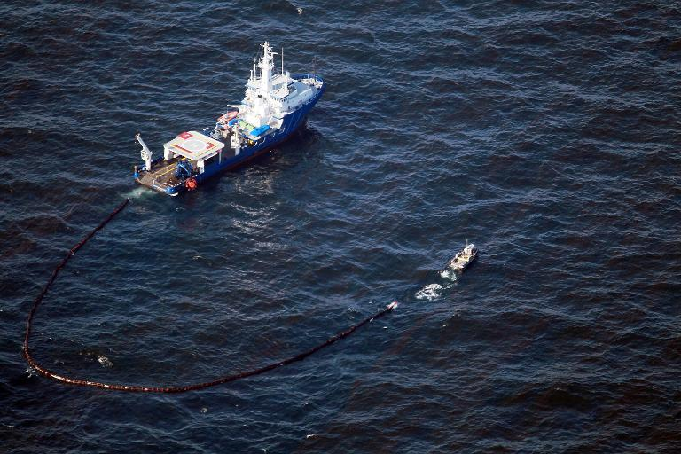 Boats pull an oil boom behind them as they skim the oil from the surface near where the Deepwater Horizon oil platform sank, on May 9, 2010 in the Gulf of Mexico