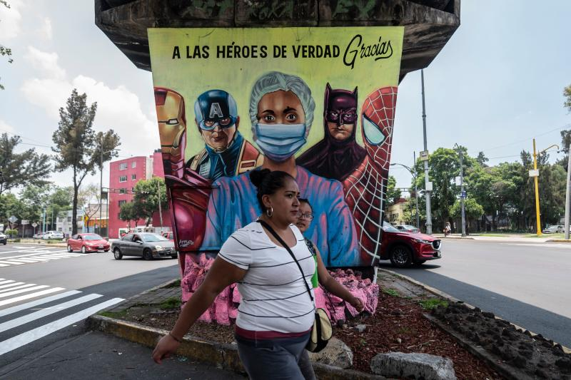 A woman walks past a mural showing a health worker and US superheroes, in Mexico City, on July 21, 2020, amid the COVID-19 novel coronavirus pandemic. (Photo by Pedro PARDO / AFP) (Photo by PEDRO PARDO/AFP via Getty Images)