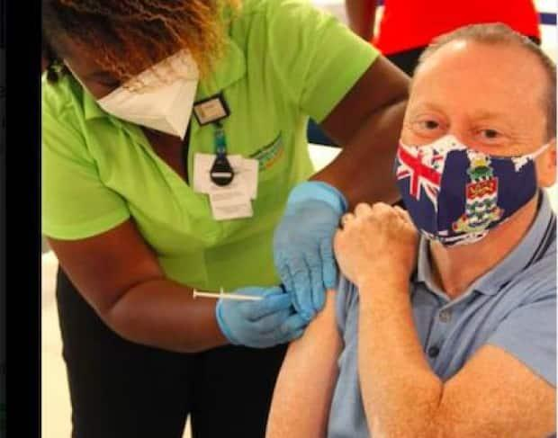 Martyn Roper, the British governor of the Cayman Islands, receives his second and final dose of Pfizer vaccine on January 28, 2021.