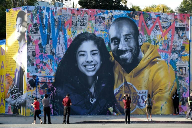 People stop to take pictures in front of the new mural by French artist Mr. Brainwash picturing Kobe Bryant and his daughter Gigi in Los Angeles on January 31, 2020