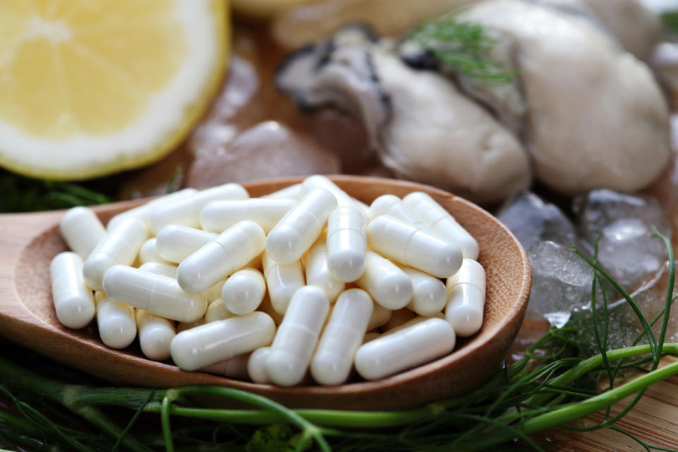 Zinc supplement capsules sit in a bowl in front of a fresh oyster and sliced lemon.